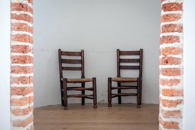 Duas cadeiras de escola marrom com parede branca no fundo em luz natural