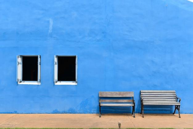 Duas cadeiras de madeira em frente a parede de gesso azul