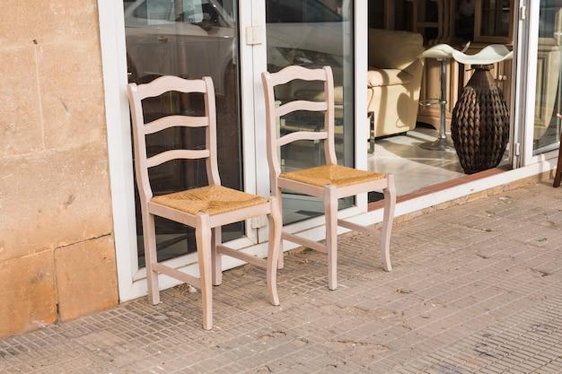 Duas cadeiras de madeira velhas em pé no quintal.