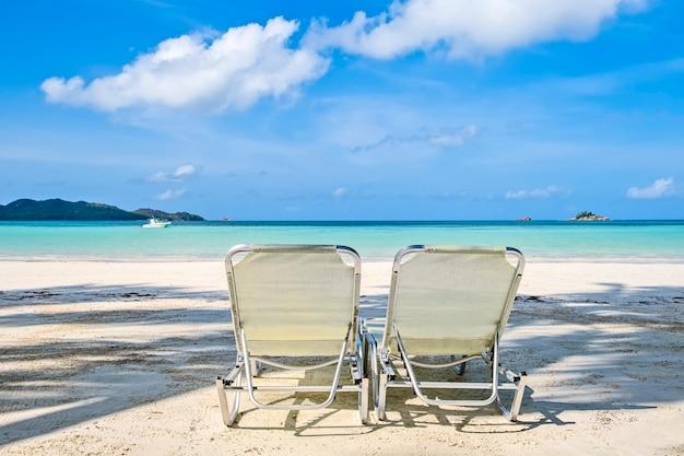 Duas cadeiras de praia brancas em uma praia de areia tropical, copie o espaço