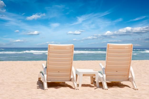 Duas cadeiras de praia do sol na costa perto do oceano