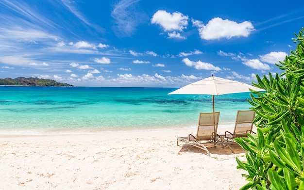 Duas cadeiras de praia e guarda-sol branco na idílica praia de areia tropical, seychelles