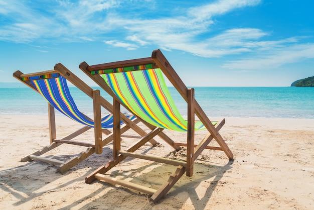 Duas cadeiras de praia na areia branca com céu azul e fundo do mar do verão.