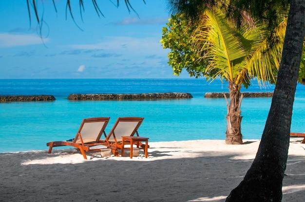 Duas cadeiras de praia na praia de areia branca tropical