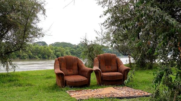 Duas cadeiras estão nas margens do rio, há árvores ao redor e um tapete na frente