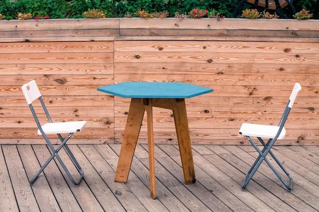 Duas cadeiras modernas brancas vazias com mesa azul no chão de madeira do teatro ninguém está sentado
