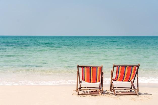 Duas cadeiras na praia perto do mar. fundo de conceito de verão e férias