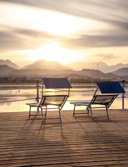 Duas cadeiras no cais com vista para o pôr do sol entre as montanhas. um lugar de descanso e relaxamento.