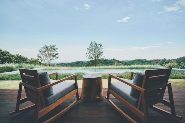 Duas cadeiras para relaxar com montanhas verdes profundas e céu azul claro