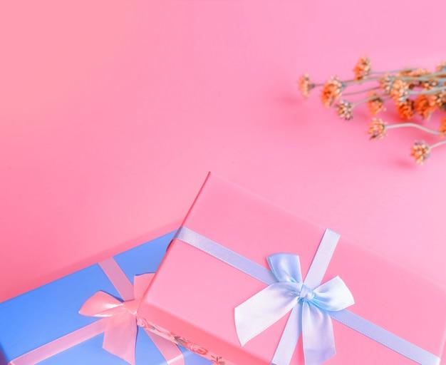 Duas caixas de azul e rosa em primeiro plano são amarradas com fitas de cetim