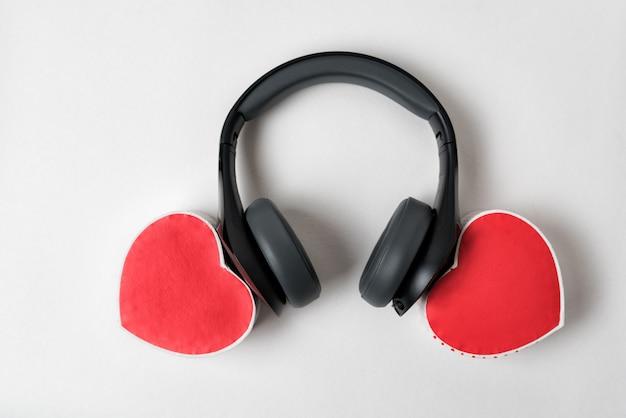 Duas caixas de forma de coração e fones de ouvido. ouça o seu coração. vista do topo