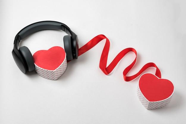 Duas caixas de forma de coração, fita vermelha e fones de ouvido na. corações de conexão