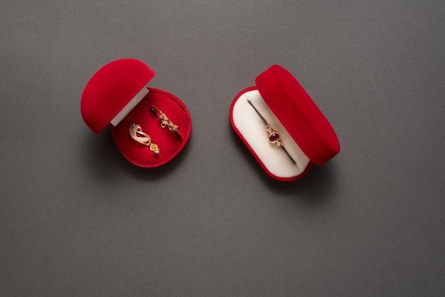 Duas caixas de joia vermelhas com joia em um fundo preto. vista do topo