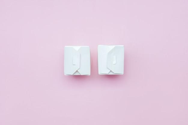 Duas caixas de papel branca comida take-away na caixa de papel branco de fundo rosa com traçado de recorte