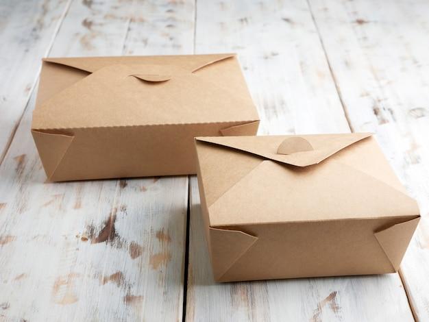 Duas caixas de papel para comida para viagem, isoladas em uma mesa de madeira