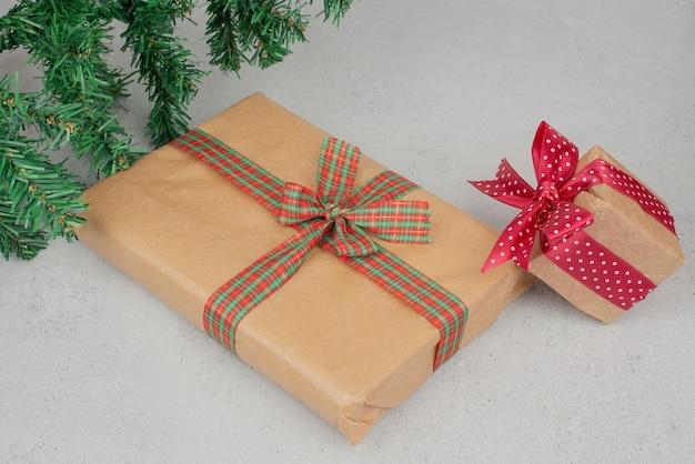Duas caixas de presente bonito com enfeites verdes na superfície cinza.