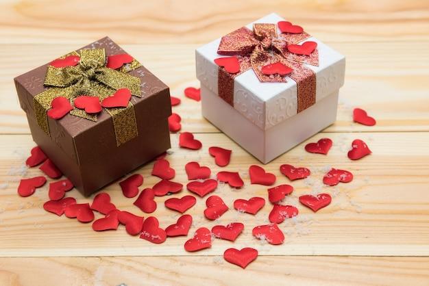 Duas caixas de presente cheias de mini corações vermelhos e neve falsa na madeira, com espaço de cópia para o texto. valentine concept para compras online presentes durante o inverno. conceito do presente packshot.