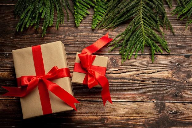 Duas caixas de presente com laço de fita vermelha em fundo de madeira