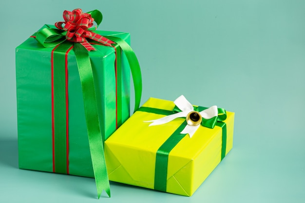 Duas caixas de presente com laço em fundo verde claro