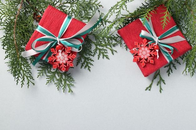 Duas caixas de presente de papel vermelho de natal com flocos de neve e fitas na superfície clara.