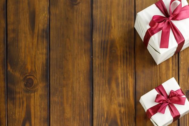 Duas caixas de presente em uma mesa de madeira marrom. fitas vermelhas nas caixas