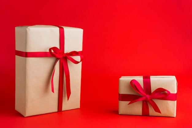 Duas caixas de presente marrom com fitas vermelhas. presente de natal ou aniversário.