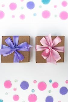 Duas caixas de presente no fundo festivo de confetes pastel.