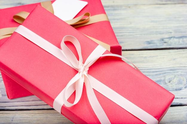 Duas caixas embrulhadas em papel de presente rosa e amarradas com uma fita branca.
