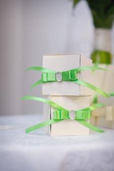 Duas caixas, presente com laço verde.
