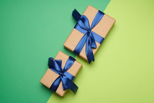 Duas caixas retangulares embrulhadas em papel pardo e amarradas com uma fita de seda com um laço