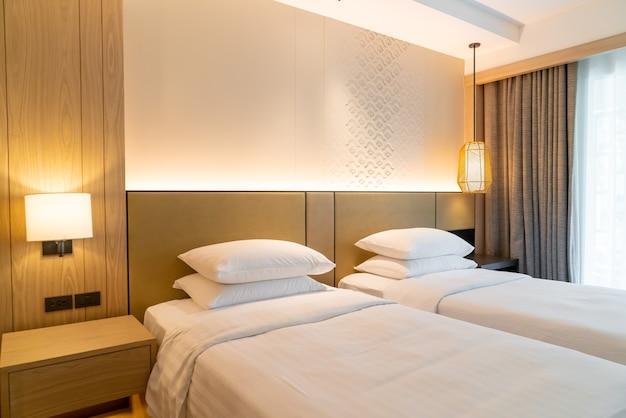 Duas camas com travesseiros em quarto de hotel resort
