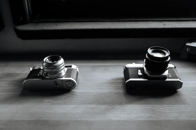 Duas câmeras de filme retrô estão sobre uma mesa de madeira. preto e branco
