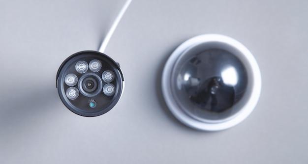 Duas câmeras de segurança em fundo cinza.