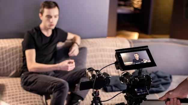 Duas câmeras de vídeo profissionais em um tripé capturando um homem falando sentado no sofá em casa. trabalhando em casa