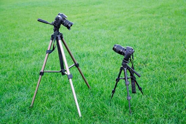 Duas câmeras fotográficas slr pretas em tripés se olham no parque no fundo da grama verde