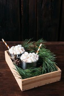 Duas canecas com cacau e marshmallows em um fundo marrom