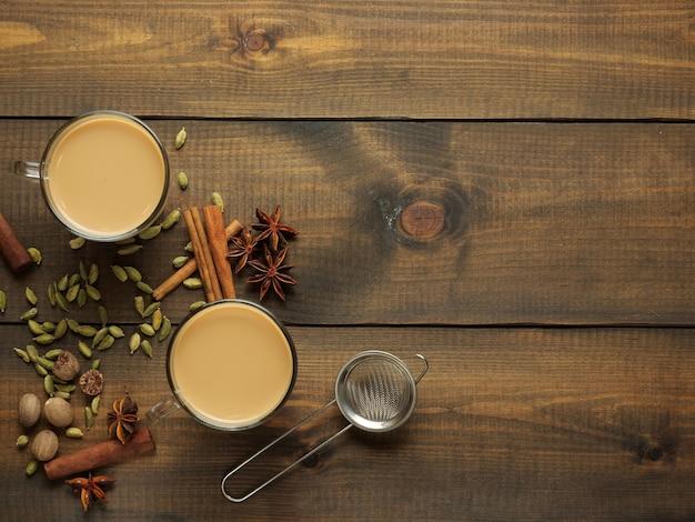Duas canecas com chá masala ficam sobre uma mesa de madeira com especiarias. vista do topo.