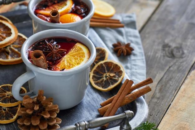 Duas canecas com vinho quente de natal com frutas cítricas e especiarias