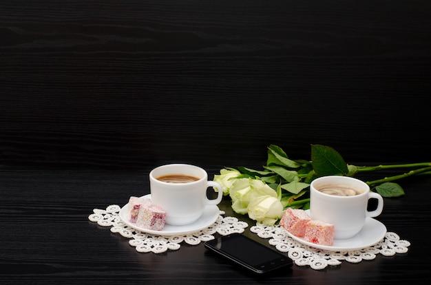 Duas canecas de café com leite, smartphone, rosas brancas em um fundo preto. espaço para texto.