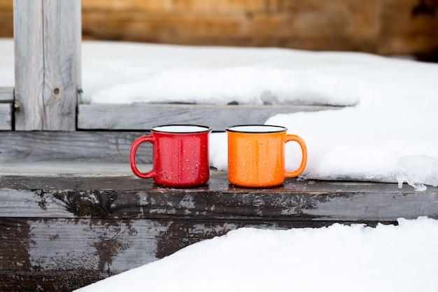 Duas canecas de café na varanda de uma casa de madeira. temporada de outono e inverno.