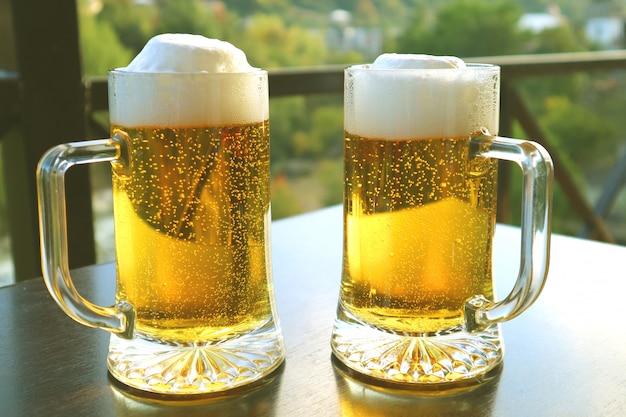 Duas canecas de cerveja gelada na mesa dos assentos ao ar livre