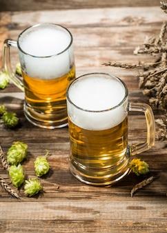 Duas canecas de cerveja na mesa de madeira com lúpulo
