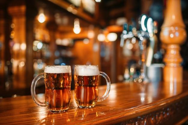Duas canecas de cerveja no balcão de madeira do bar