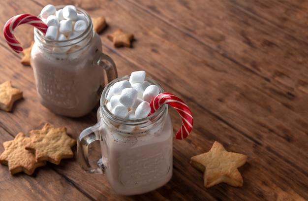 Duas canecas de vidro com chocolate, marshmallows, cana-de-açúcar e biscoitos de gengibre em um fundo de madeira.