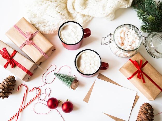 Duas canecas vermelhas com bebida quente e marshmallows, cartão de papel para carta, envelope e decoração de natal. postura plana para feliz natal ou feliz ano novo. vista do topo. copie o espaço
