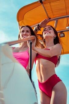 Duas capitãs. vista de baixo ângulo de garotas jovens e atraentes rindo em pé no convés de um iate e olhando para frente