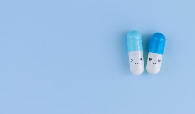 Duas cápsulas brancas e azuis com caras engraçadas na vista superior do fundo azul