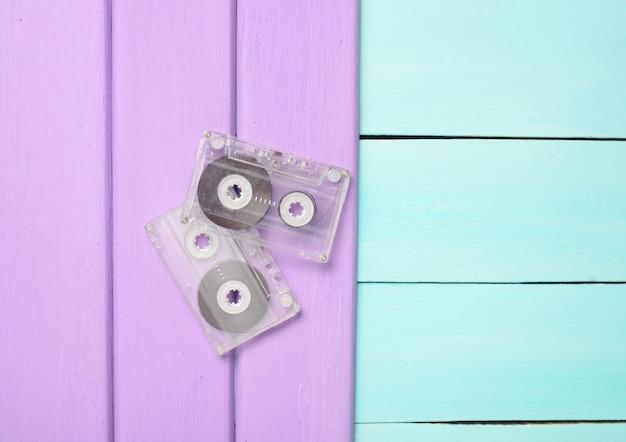 Duas cassetes áudio retrô dos anos 80 em um fundo de madeira violeta azul. vista do topo.