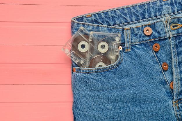 Duas cassetes de áudio no bolso da calça jeans em uma superfície de madeira rosa. tecnologia de mídia dos anos 80.