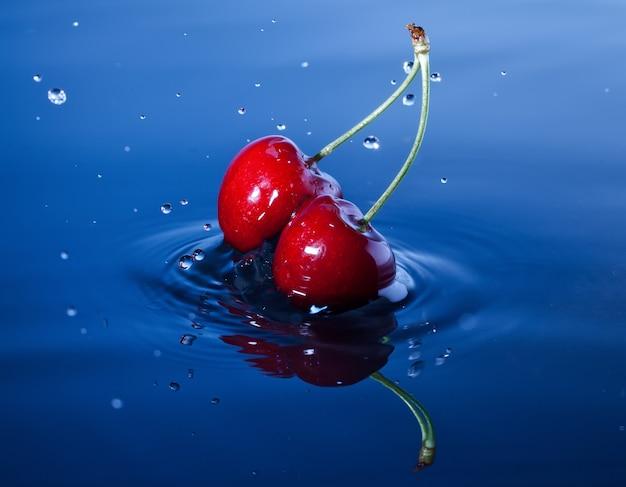 Duas cerejas caem profundamente na água com um respingo.